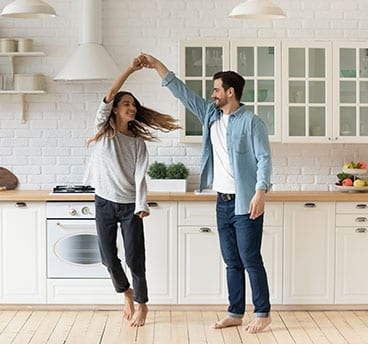 couple dancing in new remodeled white kitchen